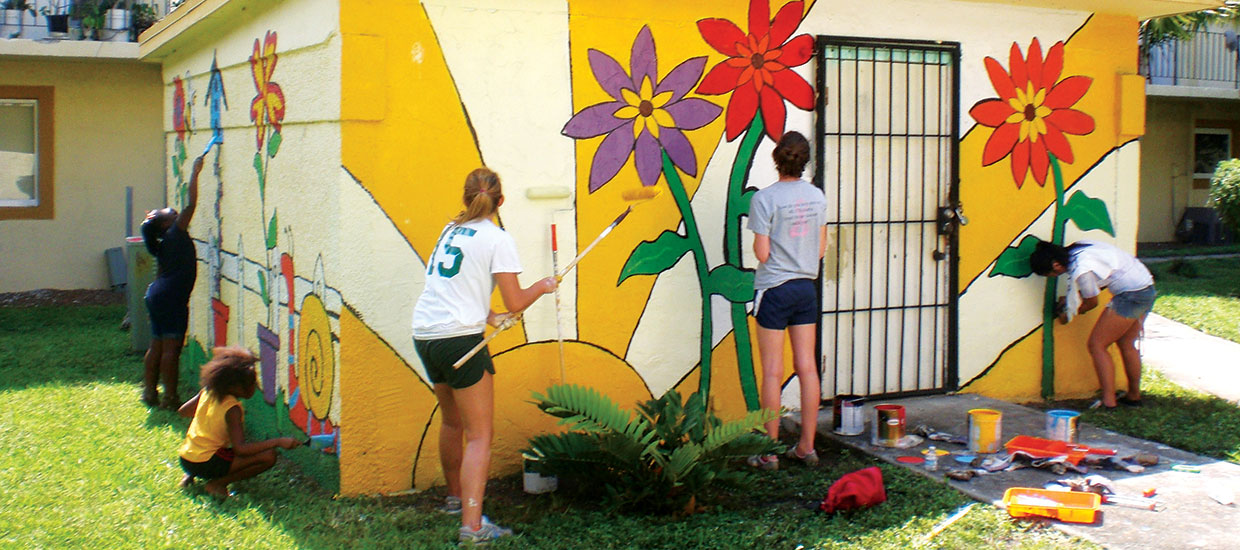 Students painting wall flowers