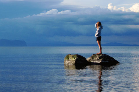 Girl on rock in the middle of ocean