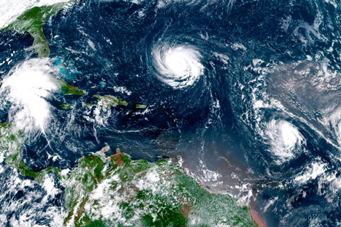 A satellite image from the National Hurricane Center shows three storms across the Atlantic—hurricanes Florence, Isaac and Helene.