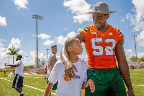 Hurricanes football linebacker Patrick Joyner, Jr. with a participant of the program's free youth football camp, held June 19 at Harris Field Park in Homestead.