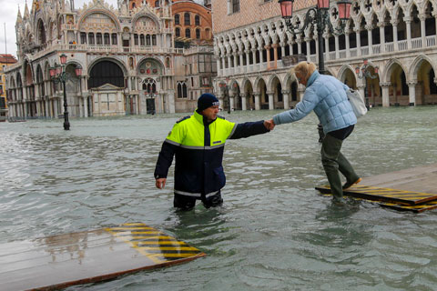 A city worker helps a woman who decided to cross St. Mark's Square on a gangway, in Venice, Italy, Sunday, Nov. 17. Photo: Associated Press