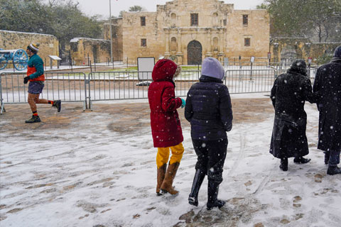 People walk through the snow as they pass the Alamo, Thursday, Feb. 18, in San Antonio. Photo: The Associated Press
