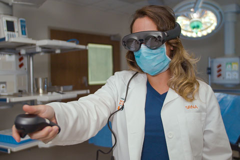 School of Nursing and Health Studies student Jackie Ferreira wears Magic Leap goggles, which the school is using to develop an application to help familiarize nurse anesthesia students with a hospital operating room. Photo: TJ Lievonen/University of Miami