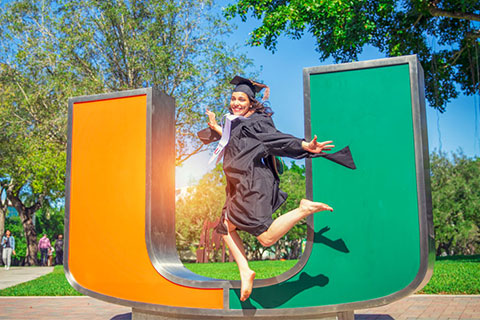 Gabby Serrano jumps for joy as she celebrates her graduation from the Miami Business School