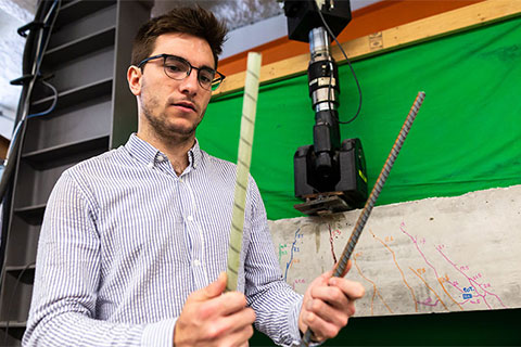Civil engineering Ph.D. candidate Alvaro Ruiz Emparanza examines bars made from glass fiber