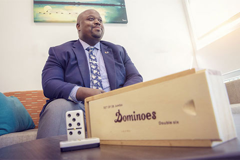 Dean of Students Ryan C. Holmes prepares for a game of dominoes