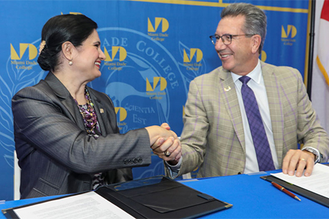 Lenore Rodicio, executive vice president and provost of Miami Dade College, shakes hands with Jeffrey L. Duerk, executive vice president for academic affairs and provost of the University of Miami, following Tuesday's signing ceremony.