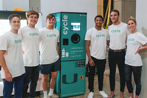 Cycle Technology team members Anwar Khan, Connor Pohl, Harrison Mount, Noah Barrows, Colin Hively, and Julie Young standing with their reverse-vending machine in the breezeway of the Miami Herbert Business School. Photo courtesy of Connor Pohl
