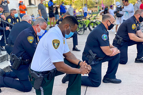 Police chiefs from across Miami-Dade County kneel in prayer at the conclusion of the protest in Coral Gables. Photo: Roy Ramos - Reporter, WPLG